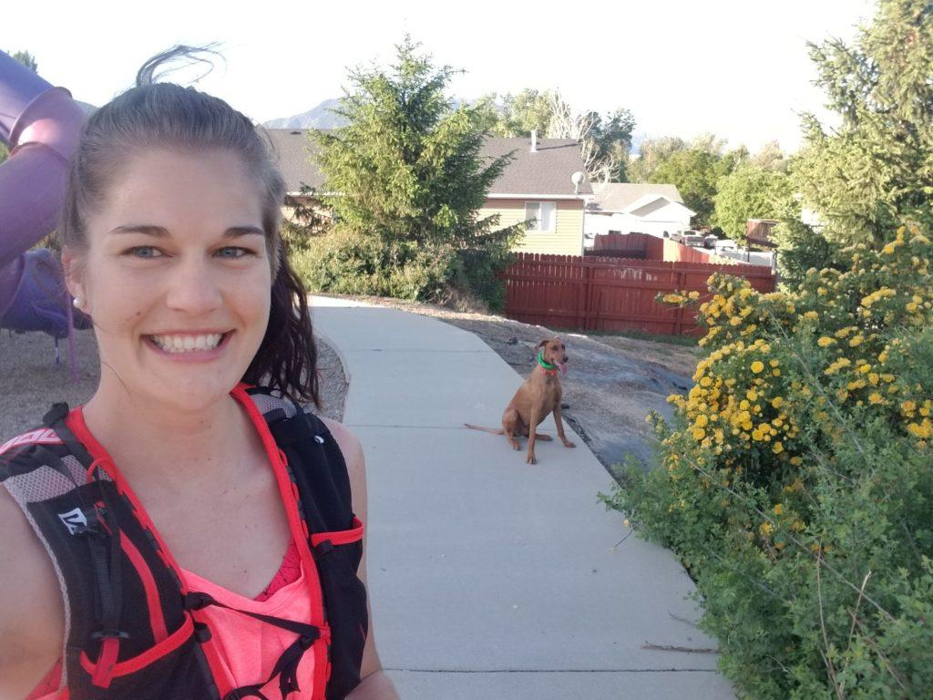 Girl running with her dog wearing a salomon running vest
